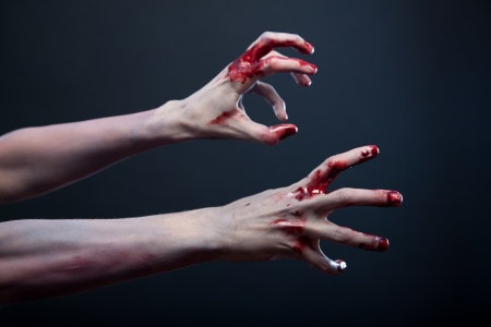 Photo for Zombie stretching his bloody hands, studio shot over gray background  - Royalty Free Image