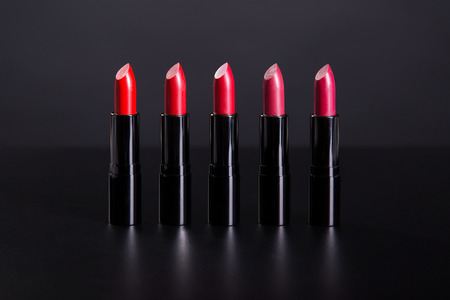 Photo pour Set of bright lipsticks in shades of red color, studio shot on black background - image libre de droit