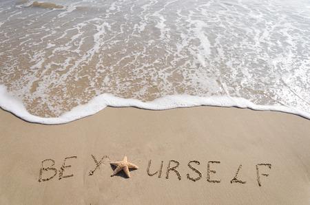 Foto de SignBe Yourself with starfish on the sandy beach by the ocean - Imagen libre de derechos
