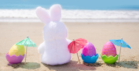 Photo for Easter bunny and color eggs with cocktail umbrellas on the sandy beach by the ocean - Royalty Free Image