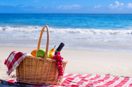 Photo pour Picnic background with basket and fruits by the ocean - image libre de droit