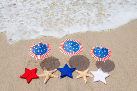 Photo pour Patriotic USA background with starfishes and decorations on the sandy beach - image libre de droit