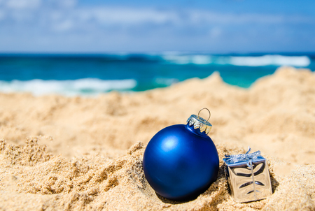 Photo for Merry Christmas and Happy New Year background with gift and ball on the tropical beach near ocean in Hawaii - Royalty Free Image