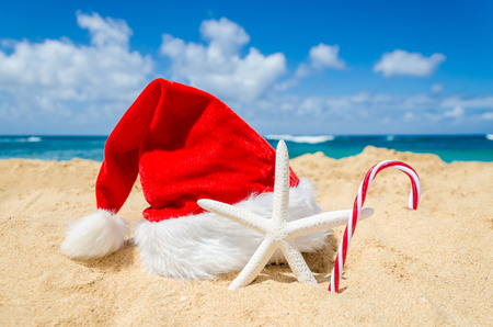 Foto de Merry Christmas and Happy New Year background with Santa Claus Hat, candy and starfish on the tropical beach near ocean in Hawaii - Imagen libre de derechos