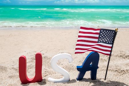 Photo pour Patriotic USA background with flag on the sandy beach near ocean - image libre de droit