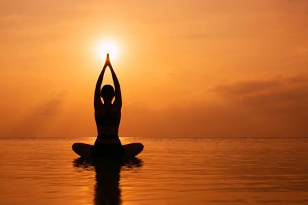 Photo pour Silhouette young woman practicing yoga on the beach at sunset - image libre de droit