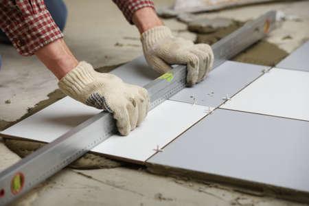 Photo pour Tiler installs ceramic tiles on a floor - image libre de droit