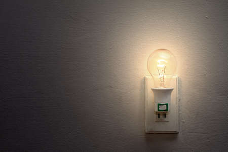 Weak light bulb and socket on the white wall