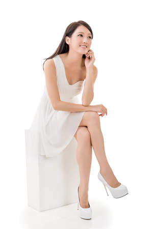 Photo pour Attractive young Asian beauty in white dress sit on a box, full length portrait isolated on white. - image libre de droit