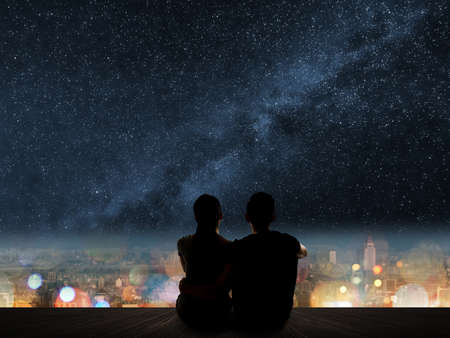 Foto de Silhouette of young Asian couple sit on wooden ground above the city under stars. - Imagen libre de derechos