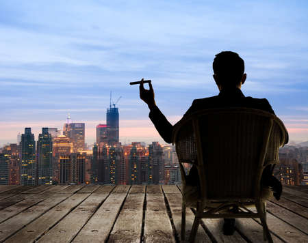 Foto de Silhouette of businessman sit on chair and hold a cigar and looking at the city in night. - Imagen libre de derechos