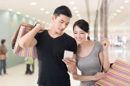 Photo pour Young Asian couple shopping and looking at cellphone, closeup portrait. - image libre de droit