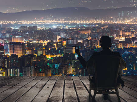 Photo pour Silhouette of businessman sit on chair and hold a cigar and looking at the city in night. - image libre de droit