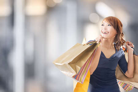 Foto de Cheerful shopping woman of Asian holding bags. - Imagen libre de derechos
