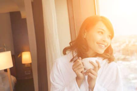 Foto de Asian woman holding a cup of coffee in the morning. - Imagen libre de derechos