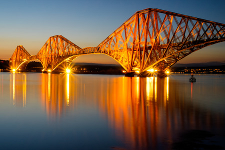 The Forth rail bridge illuminated at dawn
