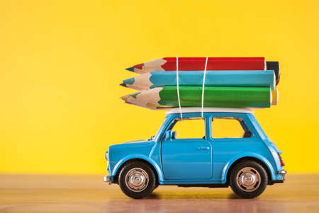Photo pour Miniature figure toy car Mini Morris carrying colored pencils on roof on yellow background in studio. Education and art concept. - image libre de droit