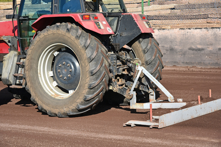 Photo pour Tractor smooths the way on the dirty sport track - image libre de droit