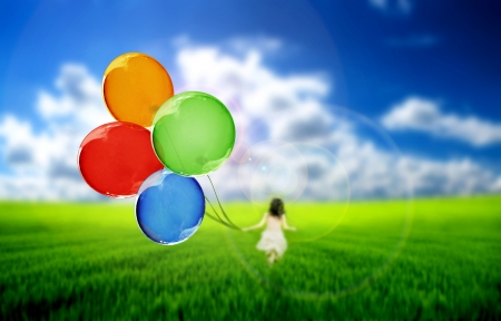 Photo for Child on a green meadow playing with colored balloons  - Royalty Free Image