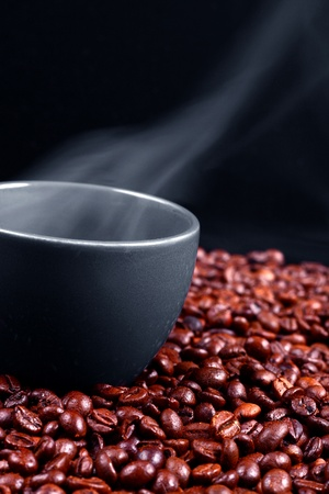 A grey cup with steaming coffee over roasted coffee beans, dark background