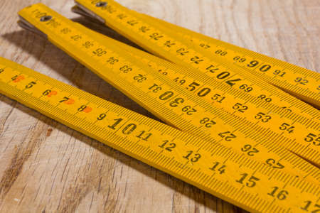 Photo for Yellow measuring stick on an old wooden table - Royalty Free Image