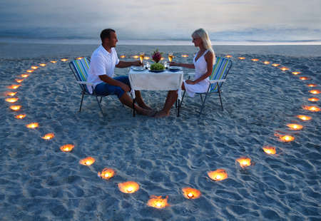 Photo pour A young lovers couple share a romantic dinner with candles heart on the sea sand beach - image libre de droit
