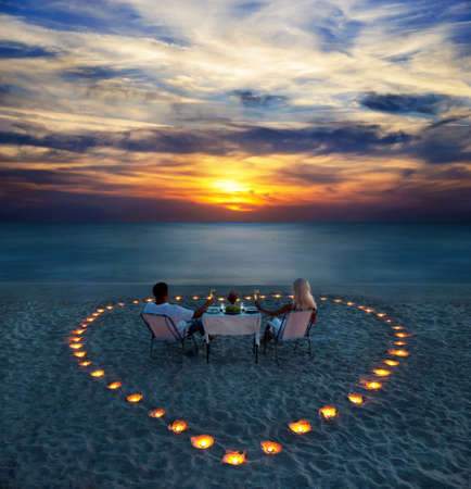 Photo for A young couple share a romantic dinner with candles heart on the sea sand beach - Royalty Free Image