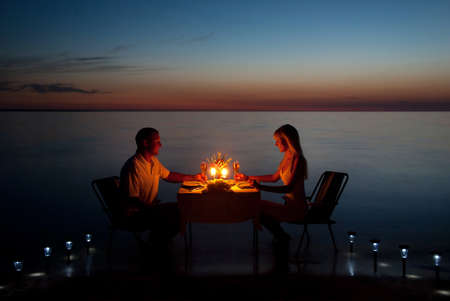 Foto de A young couple share a romantic dinner with candles on the sea sand beach - Imagen libre de derechos