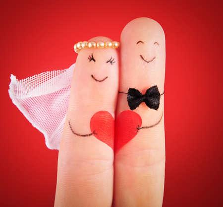 Foto de wedding concept - newlyweds painted at fingers against red background - Imagen libre de derechos