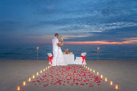 Foto de Young couple share a romantic dinner with candles, torches and way or rose petals at sea sandy beach against sunset - Imagen libre de derechos