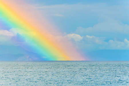 Foto de Beautiful seascape with big bright rainbow in clouds after the rain above the sea waves surface and mountains - Imagen libre de derechos