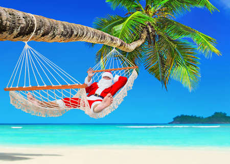 Foto de Santa Claus relaxing at sun in white cozy mesh hammock under coconut palm tree shadow at tropical paradise sandy ocean beach - New Year and Christmas travel holidays concept - Imagen libre de derechos