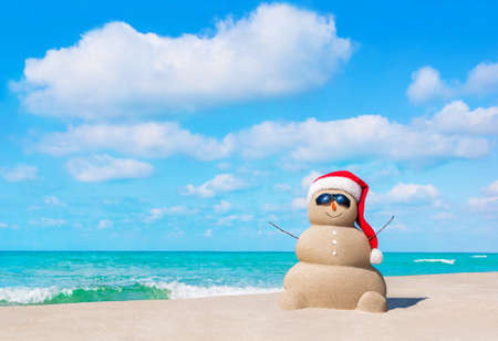 Foto de Positive sandy snowman in red Santa Claus hat and sunglasses at cloudy sunny ocean beach. Happy New Year and Merry Christmas travel destinations concept for tropical vacations. - Imagen libre de derechos