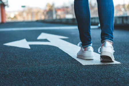 Foto de Make decision which way to go. Walking on directional sign on asphalt road. Female legs wearing jeans and white sneakers. - Imagen libre de derechos