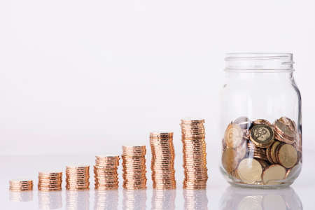 Foto de Image of Golden coins stacked and penny jar over white background - Imagen libre de derechos