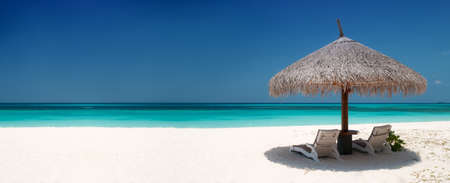 Foto de Beach Chairs and Umbrella on a beautiful island, panoramic view with much copyspace - Imagen libre de derechos
