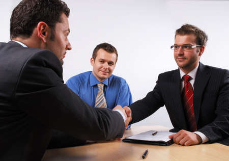 Three businessmen sitting at a table negotiating and signing a contract. handskake.