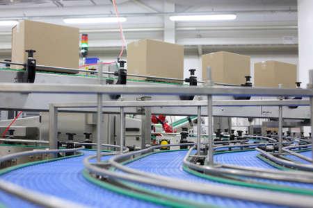 Photo pour  Cardboard boxes on conveyor belt in factory - image libre de droit