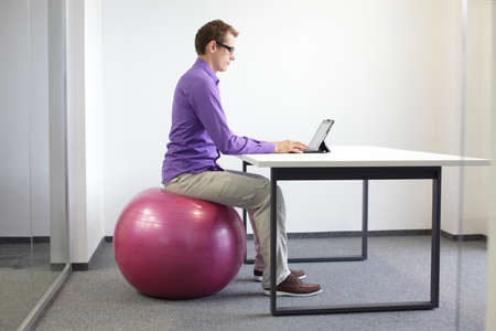 Photo pour  man on stability ball working with tablet - correct sitting position at workstation   - image libre de droit