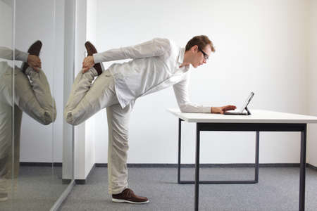 Foto de leg exercise durrng office work - standing man reading at tablet in his office  - Imagen libre de derechos