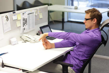 Foto de Man office worker,exercising during work with tablet in his office - Imagen libre de derechos
