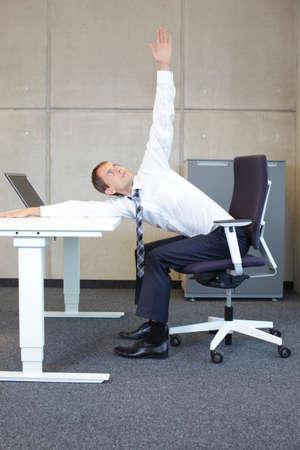 Foto de yoga in office. business man exercising in sitting position on armchair at the desk - Imagen libre de derechos