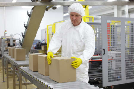 Photo for Manual worker in white uniform,cap and yellow gloves, at production line dealing with boxes - Royalty Free Image