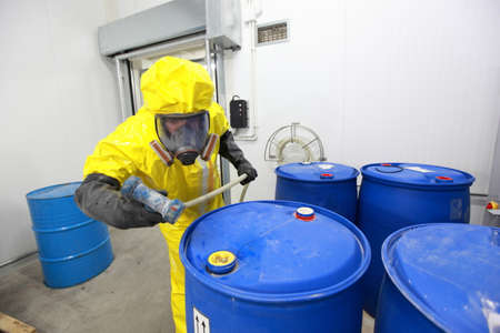 Photo pour Professional in uniform preparing to fill barrels with chemicals - image libre de droit