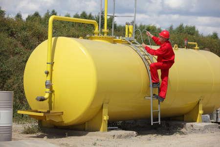 Photo pour technician in red uniform wclimbing on large fuel tank - image libre de droit