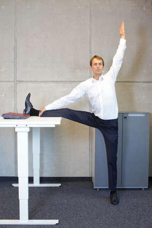 Photo pour office yoga - business man exercising at desk - image libre de droit