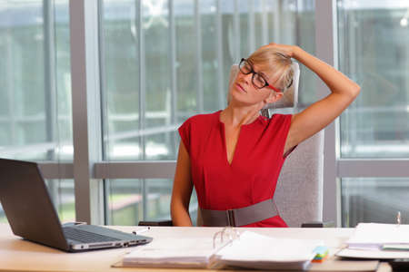 Foto de caucasian business woman in eyeglasses relaxing neck,stretching arms - short break for exercise on chair  in office - Imagen libre de derechos