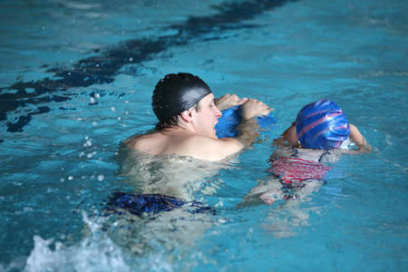 Close up of swimming lesson - child  practicing flutter kick with kick board  with instructor in  indoor swimming pool -back view