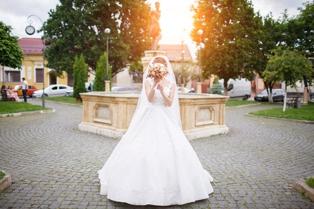 Photo pour the bride in an elegant white dress stands near a monument in the city center - image libre de droit
