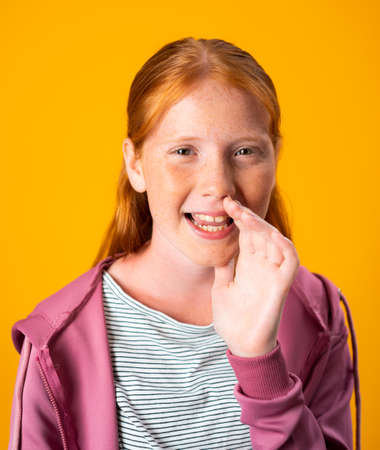 Photo for Red Hair Girl Gossiping and Telling a Secret With Hand In Mouth. Young woman with freckles and red hair is talking in a low voice, whispering a secret. Portrait of Teenager or Preteen - Royalty Free Image